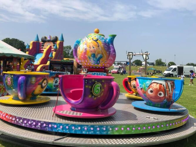 Photograph of the cups and saucers (tea cups) childrens ride. Pictured with an inflatable slide in the background, on a sunny day.