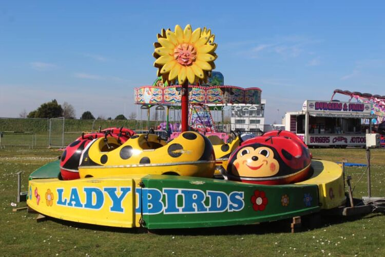 Photograph of Tuckers Funfairs Ladybirds Children's Ride, pictured on grass, with the mini chairs and a catering unit in the background
